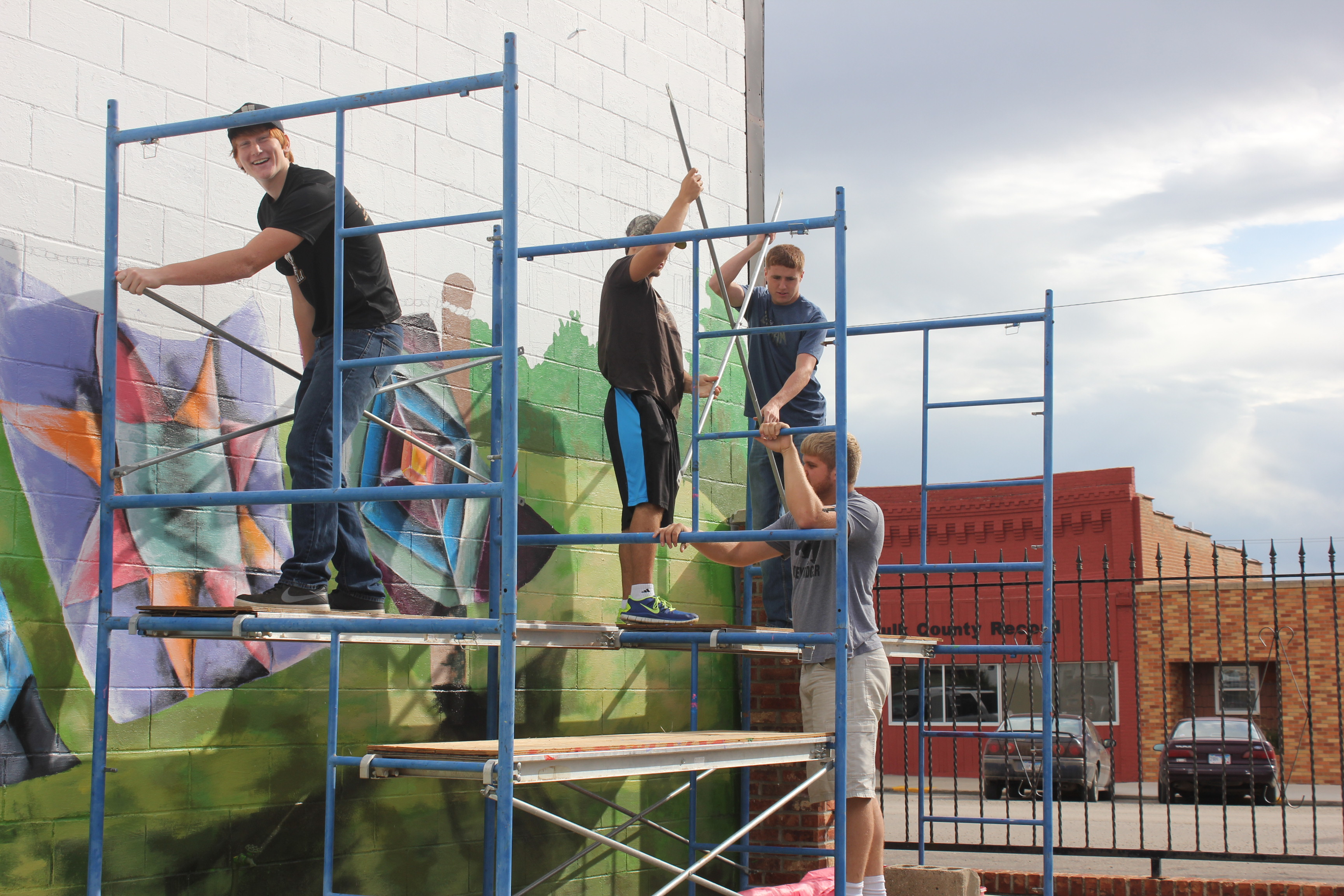 Image of young boys painting a brick exterior wall on a downtown main street. Four young men are standing on a scaffolding - one faces the camera while painting, two work with large rollers to get more paint, and one stands at the far end of the scaffold.