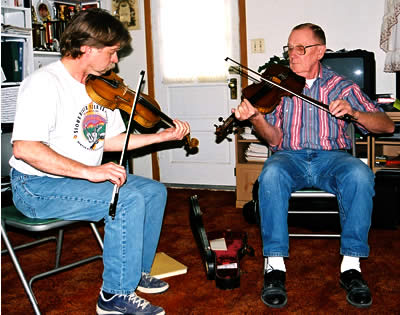 Two men seated, playing fiddle. Bill Peterson (at left) and Dwight Lamb (at right).