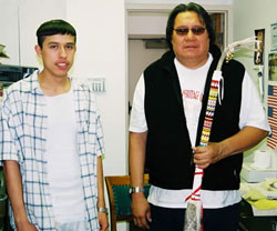 Two men (Calvin Renteria at left and Alvin Pipe on Head) standing together. Alvin hopes a beaded Deer Dance stick.