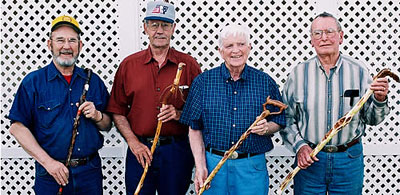 Four men standing together (from left Garold Engel, Gary Teaney, Don Green and Hilary Cole) holding canes upright