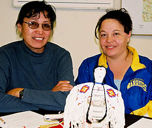 Two women (Tilda St. Pierre at left and Stephanie Sorbel) sitting. Sorbel presents beaded lakota doll.