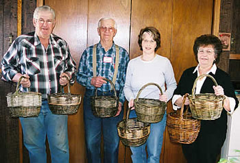 Two men stand at left of two women each holding willow baskets.