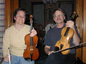 Woman (Beth Preheim at left) and man (Bill Peterson) sit side-by-side with fiddles.