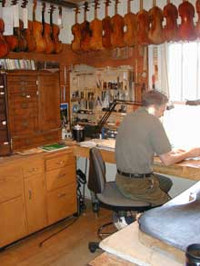 John Waddle seated at work bench working in violin repair shop. Violins hang over his head.