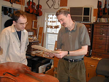Chris Unversagt and John Waddle (two men) study a violin piece in shop.