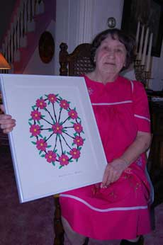 Leona Barthle (woman) with papercutting design (red flowers with green leaves and black stems)