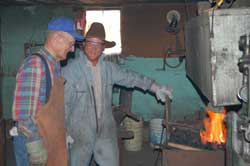 Tro men standing in front of forge (open flame) with metal tools in shop.
