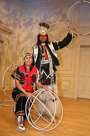 Jasmine Pickner (woman kneeling at left of) and Dallas Chief Eagle (man standing at right and behind woman) together in red and black traditional clothing with hoops.
