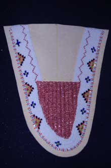 Beadwork pattern (white background with colored beads bordering curve of toe piece) on the toe piece of a moccasin