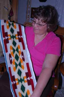 Tamara Fonder (woman) shows beadwork on a Pendleton blanket (long banner with red, dark red, orange, and green patterns)