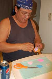 Man (Sherman Bear Ribs) seated worked on beading a turtle.