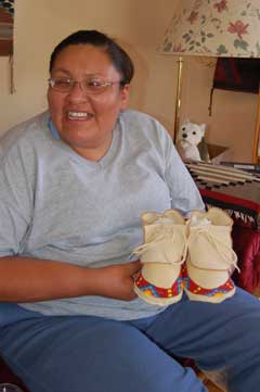 Women (Apprentice Vanessa Brings Him Back) seated with pair of moccasins, beaded across toes, on her lap.