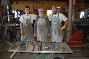 Three men standing behind low table with steel items the men made together. Master blacksmith Jack Parks (center) and apprentices.